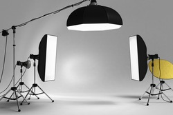 Studio lighting equipment, 3 softboxes from top and 2 sides, with copy space of your image or message on white wall environment.