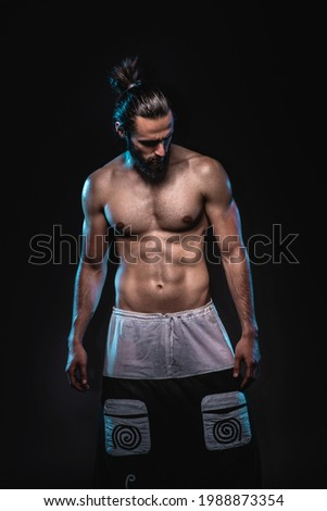 Studio lowkey portrait of a powerful muscular man. Abstract conceptual photo o a balancing physical and mental strength. Foto stock ©