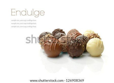 Studio macro of assorted delicious liqueur chocolates on a white background with soft shadows. Copy space.