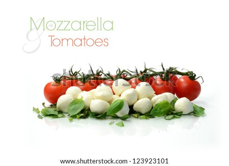Studio macro of ripe tomatoes and mozzarella balls garnished with chopped basil. Copy space.