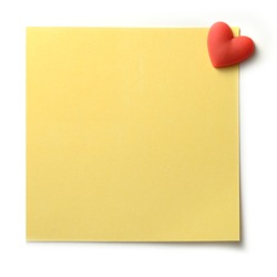 Studio macro of textured yellow post note pinned to a white background with a red heart shaped pin. Copy space.