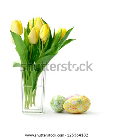 Studio macro of yellow tulips (Tulipa gesneriana) in a glass vase with decorative paper covered easter eggs against a white background. Copy space.