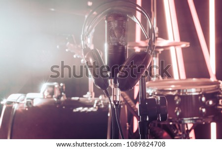 Studio microphone and headphones on a close-up stand, in a recording Studio or concert hall, with a drum set in the background in out-of-focus mode. Beautiful blurred background of colored lights. #1089824708