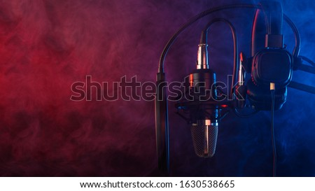 Studio microphone and headphones on mic stand against .Color disco background. Vocals and radio, podcasts.
