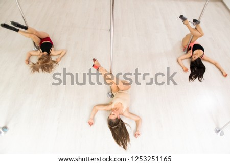 Stock Photo Studio performance of poledancing being given by three fit girls in bodysuits