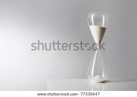 Studio photo of a hourglass on reflective table.