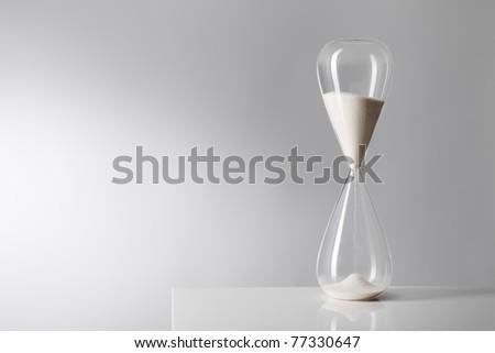 Studio photo of a hourglass on reflective table.