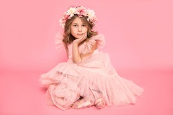 Studio photo of a small beautiful sitting girl with wreath of flowers on her head and curls of hair. Background, accessories, dress are pink. Hairdressing salon. Children's cosmetic. Kid's psychology