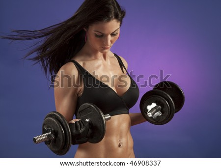 Studio photo of attractive woman exercising with dumbbell free weights.