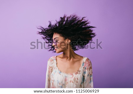 Studio photo of inspired african lady dancing with eyes closed. Indoor portrait of relaxed black girl isolated on purple background. #1125006929
