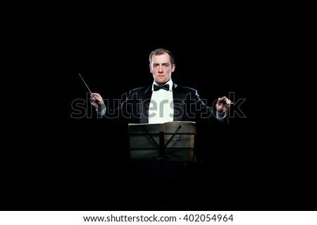 Studio photo of music conductor holding his baton #402054964