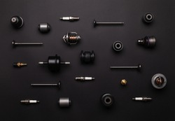Studio photography - a lot of automotive parts: valves, spark plugs, silent blocks, thermostats, filter, sensors, ball bearings, lie in straight rows on a flat surface isolated on a black background.