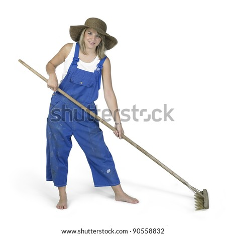 Studio photography of a blond girl dressed in a blue boilersuit with a rake in white back - stock photo