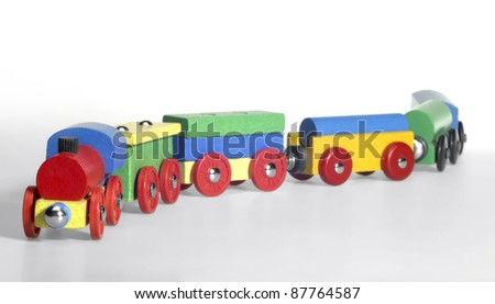 studio photography of a colorful wooden toy train in light back