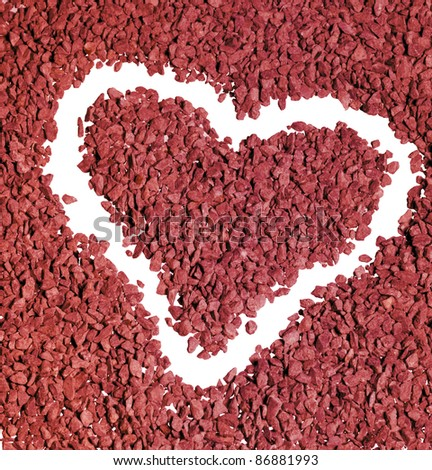 studio photography of a heart shape carved out of a background made of red gravel stones