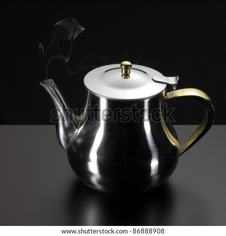 studio photography of a metallic tea pot and some damp in dark back