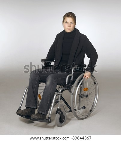 studio photography of a young woman sitting in a wheelchair in light grey back