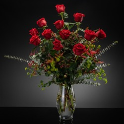 Studio photography of floral arrangements on a gray backdrop with a dozen red roses