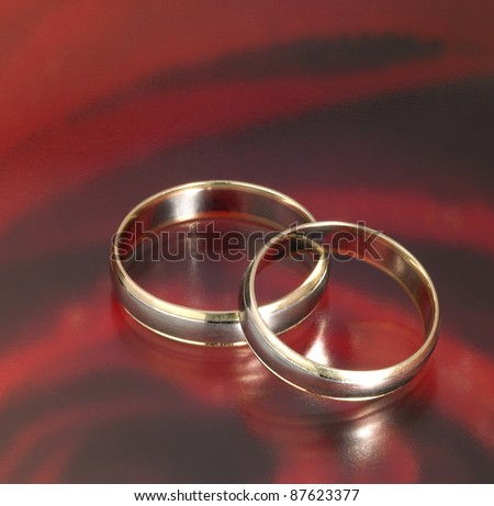 studio photography of two golden wedding rings on each other in reflective red abstract back