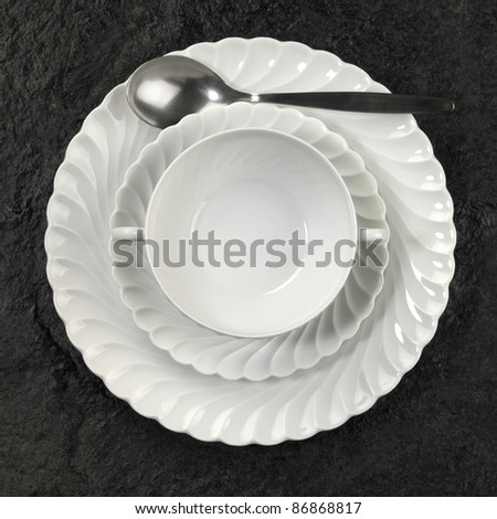 Studio photography of white porcelain plates and spoon on dark stone surface seen from above