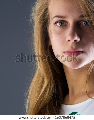 studio photography portrait of a girl of 14 years old beautiful face, Age of innocencel A closeup of a beautiful little girl is laying down with her hair out for a salon hairstyle or innocence concept