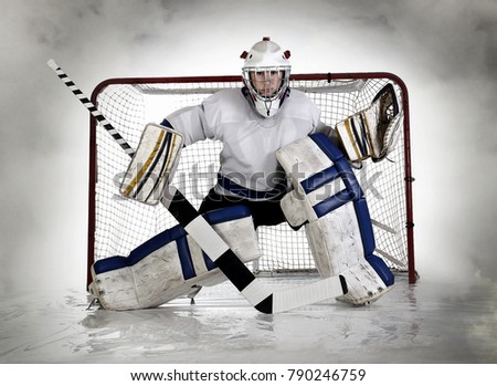 Studio pic of a female, teenage hockey goalie and net with a fog background.