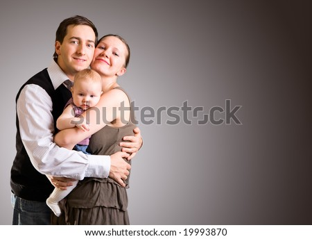 Studio picture of happy young parents and 4 months old baby girl over dark gray background