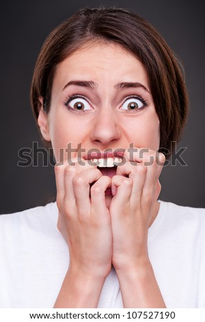 studio picture of shocked and screaming woman over dark background