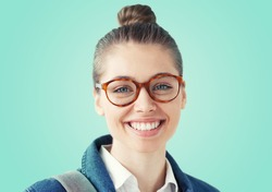 Studio portait of young pretty college student girl, wearing glasses, isolated on mint blue background