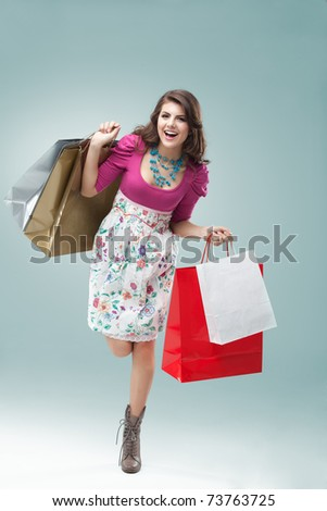 studio portrait of a beautiful young woman, in a colourful outfit, holding in her hands a few shopping bags. she is hopping on one foot, laughing and looking very happy.