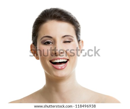 Studio portrait of a beautiful young woman laughing amd winking her right eye, isolated on white