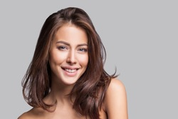 Studio portrait of a beautiful young woman with brown hair. Pretty fashion model girl with perfect fresh clean skin. Beauty, wellness, people, healthy lifestyle and skin care concept