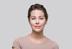 Studio portrait of a beautiful young woman with brown hair. Pretty model girl with perfect fresh clean skin. Beauty, healthy lifestyle and skin care concept