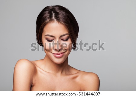Studio portrait of a beautiful young woman with brown hair. Pretty model girl with perfect fresh clean skin. Beauty and skin care concept