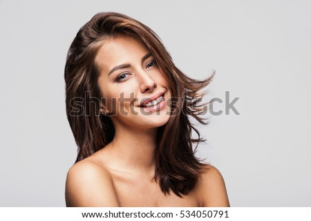 Studio portrait of a beautiful young woman with long brunette hair. Pretty spa model girl with perfect fresh clean skin. Youth and skin care concept