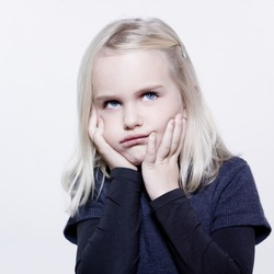 studio portrait of a caucasian cute sulk litle girl