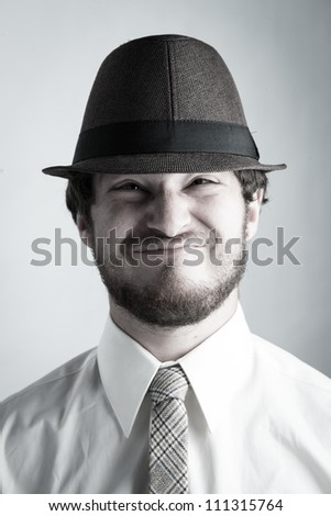 Studio portrait of a college boy wearing a hat and tie making a funny face