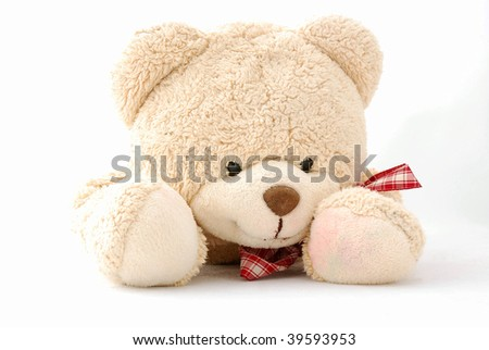 Studio portrait of a cute teddy bear for kids with happy smiling facial expression laying down and staring. Image isolated on white background.