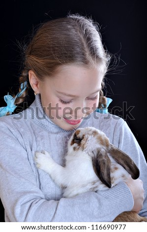 Studio portrait of a girl and a rabbit. The child looks at the animal