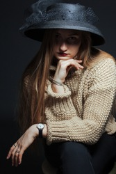 Studio portrait of a girl in a knitted sweater with a dark hat hiding her face. Shot in dark colors. The concept of isolation
