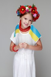Studio portrait of a girl in the Ukrainian national costume holding a flag of Ukraine on a gray background