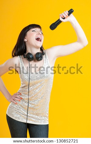 Studio portrait of a glamorous girl holding mike and singing