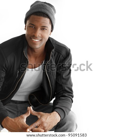 Studio portrait of a good looking happy young black man in trendy clothes against white background with copy space - stock photo