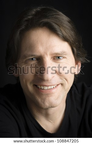 Studio portrait of a happy man smiling directly to the camera