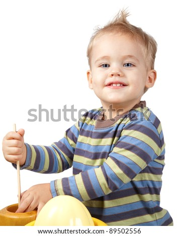 Studio portrait of a happy one year old baby boy playing with kitchen utensils.