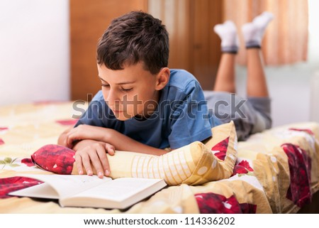 Studio portrait of a schoolboy reading a textbook while lying in bed