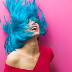 studio portrait of a sexy beautiful girl with a smile  in motion on a pink background. Girl with turquoise hair