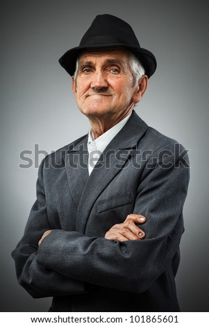 Studio portrait of a smiling old man with hat