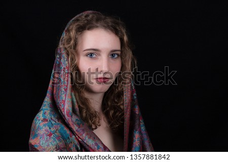 Studio portrait of a smiling teenage girl with long curly hair, wearing a colorful scarf on her head against a black background #1357881842