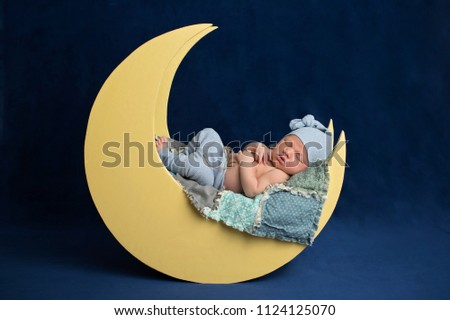Studio portrait of a ten day old newborn baby boy wearing pajama bottoms and a sleeping cap. He is sleeping on a moon shaped posing prop. #1124125070